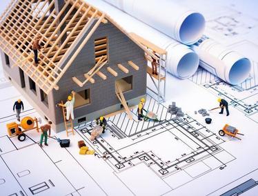 Cartoon construction workers renovating miniature home