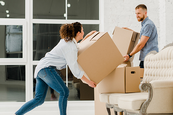 Young couple carrying boxes into residential property