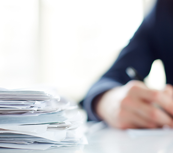 Stack of tax documents on tax expert's desk
