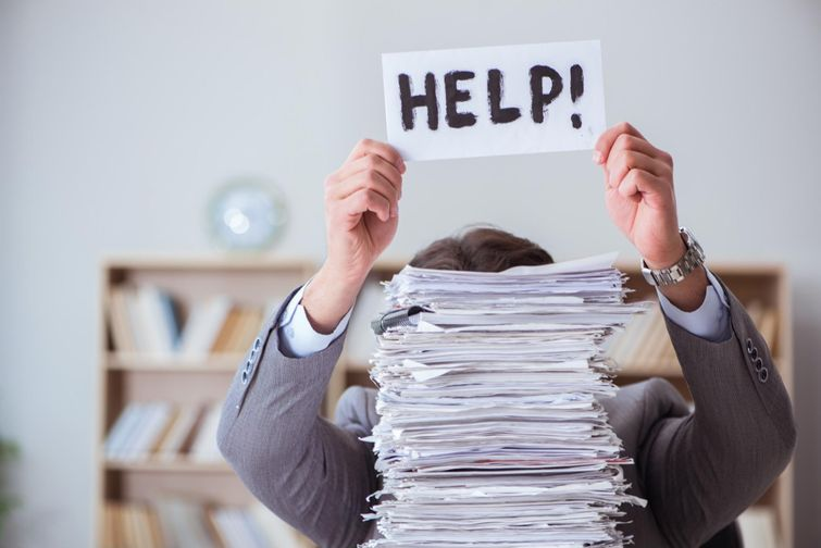"""Frustrated homeowner holding """"Help!"""" sign over stack of rebate applications"""