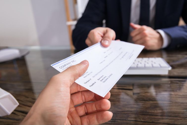 Tax expert handing cheque for GST/HST credit to client