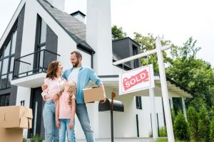 Family of first-time homebuyers holding boxes outside new Ontario home